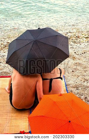 umbrella on beach with two people from behind