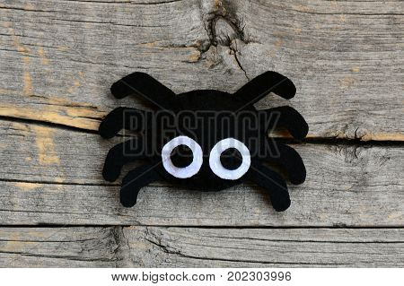 Creating a felt Halloween spider ornament. Step. Cute Halloween spider ornament isolated on a vintage wooden background. Things to make with felt sheets. Top view. Closeup