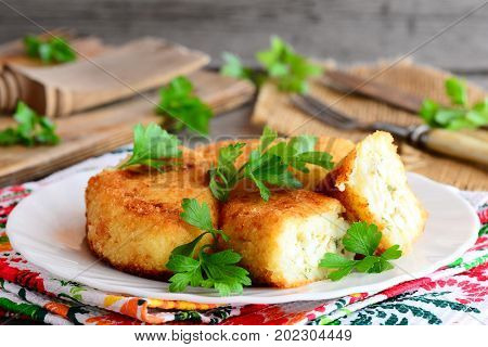 Fried vegetable cutlets with egg stuffing on a serving plate. Cutlets cooked from cauliflower and potatoes and stuffed with boiled sliced eggs. Rustic style. Closeup