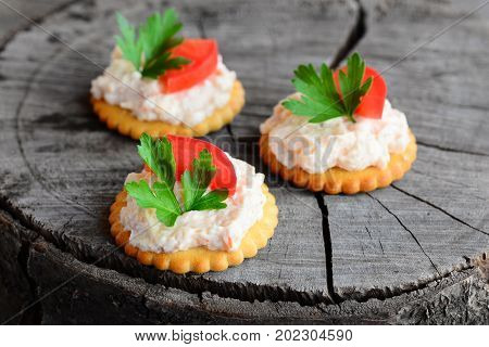 Small biscuit crackers with cream cheese on a wooden background. Quick snack from salted biscuit crackers, spicy cream cheese, fresh tomato slices and parsley. Snack buffet menu. Closeup