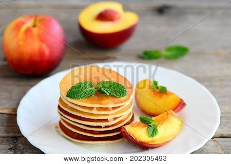 Basic pancakes with syrup and grilled nectarines on a serving plate and an old wooden table. Pancake recipe without butter. Healthy and easy breakfast for kids