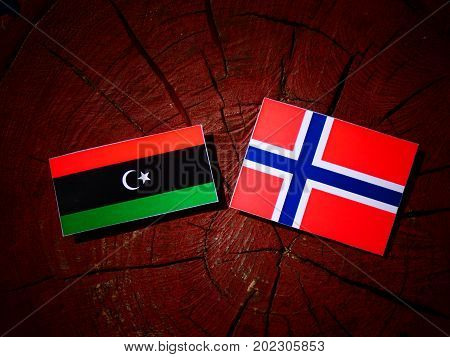 Libyan Flag With Norwegian Flag On A Tree Stump Isolated