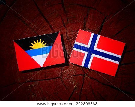 Antigua And Barbuda Flag With Norwegian Flag On A Tree Stump Isolated