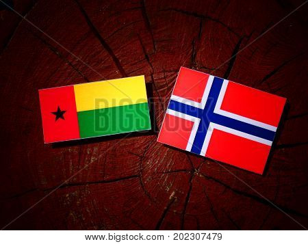 Guinea Bissau Flag With Norwegian Flag On A Tree Stump Isolated