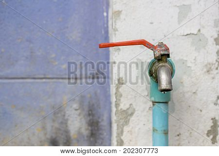 Close up to faucet water in garden on old wall background with copy space for design