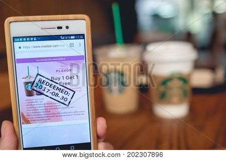 Bangkok Thailand - Aug 30 2017: Hand holding smart phone opening Starbucks Buy 1 Get 1 Free campaign Online coupon against blur Starbucks coffee cups Starbucks is the largest coffeehouse company.