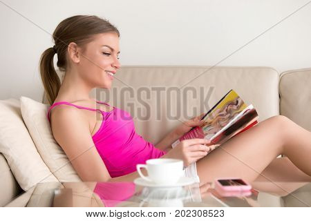 Lady lying on sofa and reading magazine. Attractive woman relaxing at home, looking for latest fashion trends, reviewing show business news, celebrities lives, examining goods catalogue at free time