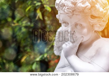 Garden decorate background concept. White vintage statue cupid in the garden with green copy space at the left side. Morning light bokeh and lens flare effect. English style garden