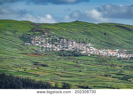 Aerial view of valley and hill with farm fields and residential houses in the Terceira island in Azores