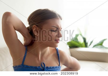 Woman with painful face expression massaging and stretching her tense neck muscles, feeling strong upper back pain, suffering from discomfort because of problems with posture. Overwork and fatigue