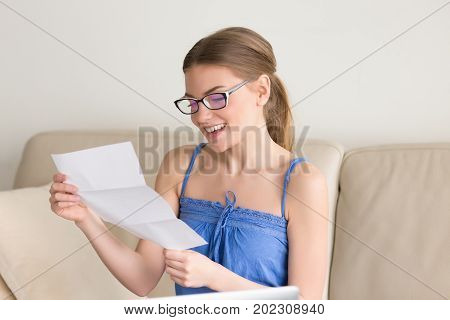 Smiling young woman in eyeglasses reading letter on sofa at home happy with good news in written notice, glad because of event invitation. Female wearing casual clothing received positive exam results