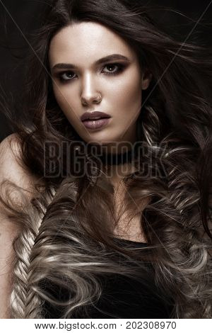 Brunette girl with a creative hairstyle braids and dark make-up. Beauty face. Photo taken in the studio.