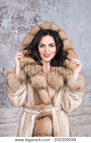 Brunette woman with jewelry wearing luxury fur coat. Fashion model girl portrait, studio shot. Winter clothes
