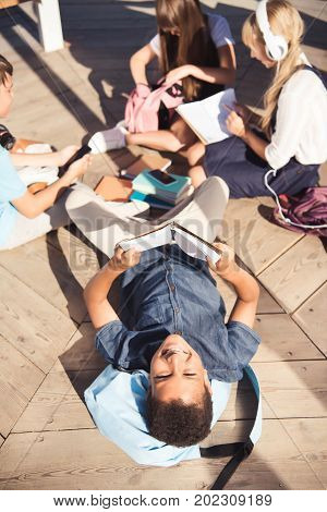 high angle view of african american teenager reading book and smiling at camera while studying with friends