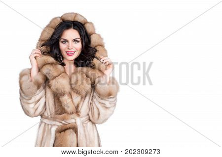 Brunette woman with jewelry wearing luxury fur coat isolated on white background, copyspace for text. Fashion model girl portrait, studio shot. Winter clothes