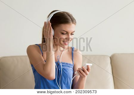 Smiling young woman in headphones using cellphone while sitting on sofa in living room and listening music, podcast or audio book. Female enjoying digital gadgets, choosing music in online audio store
