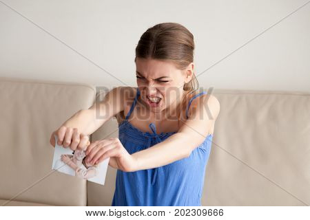 Angry woman tears her and boyfriend portrait photo in two pieces. Stressed wife hates husband because of marital betrayal, feels strong jealousy. Aggression, breakup, divorce, couple conflict concept