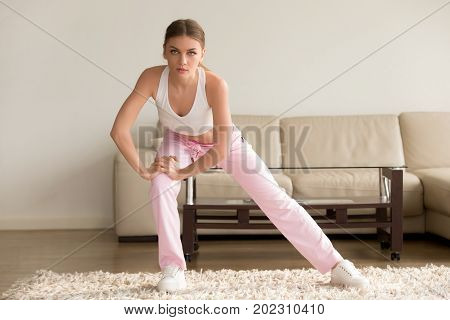 Pretty young woman in sportswear doing simple morning exercises at home. Slim lady stretching her muscles during ten minutes fitness workout in living room. Activity for health, good physical shape