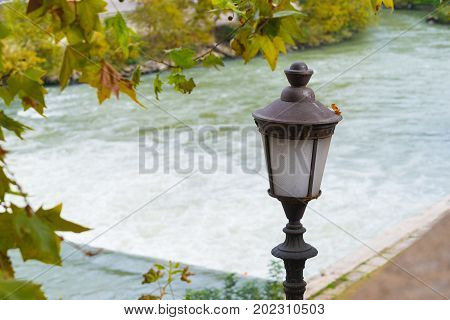 old rusty lantern with the Tiber river in the background in rome italy
