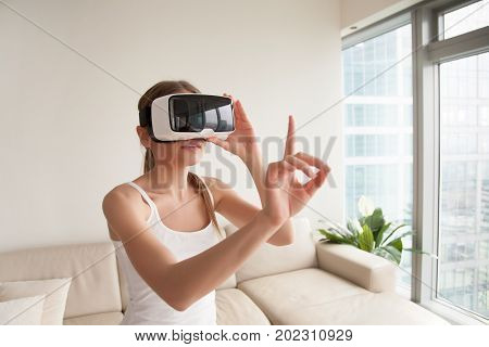 Woman in virtual reality glasses touching objects in augmented reality, interacting with 3d simulation. Lady selecting app menu items, working in virtual interface, wearing VR headset helmet at home poster