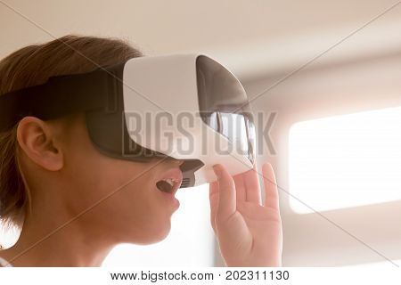 Woman in VR headset feeling surprised looking at objects inside of virtual reality, excited with effects in realistic 3d simulation, using virtual reality glasses helmet for the first time. Close up