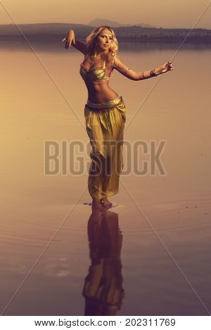 Beautiful blonde belly dancer woman on a lake in the evening. Golden colors