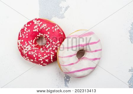 Sweet pink and white donuts on white background. Copy space