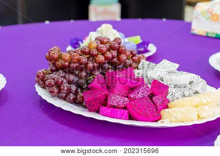 delicious  fruit , grapes, dragon fruit , melon  on the white bowl , healthy food for everybody with copy space