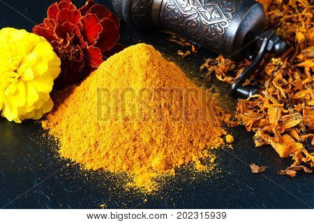 Heap of Turmeric powder over slate background