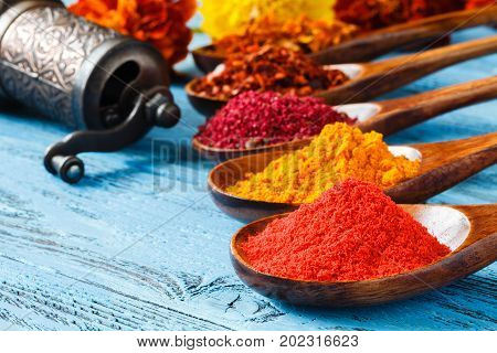 Spice In The Wooden Spoon. Red Pepper, A Turmeric, Cumin And Another On A Wooden Rural Background.