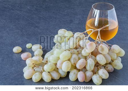 Cold white wine and green grapes on stone