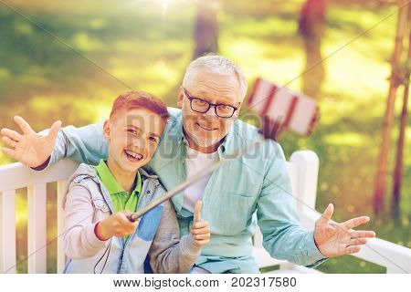 family, generation, technology and people concept - happy grandfather and grandson taking picture with smartphone selfie stick at summer park