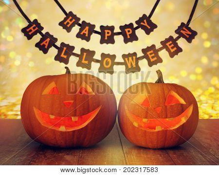 holidays, decoration and celebration concept - jack-o-lantern or pumpkins and happy halloween festive garland or banner over lights background