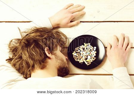 Man With Closed Eyes Lies On Light Wooden Background