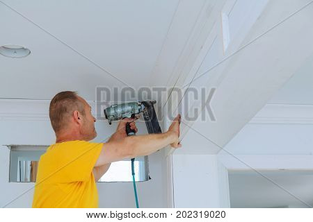 Carpenter brad using nail gun to Crown Moulding framing trim with the warning label that all power tools have on them shown illustrating safety concept