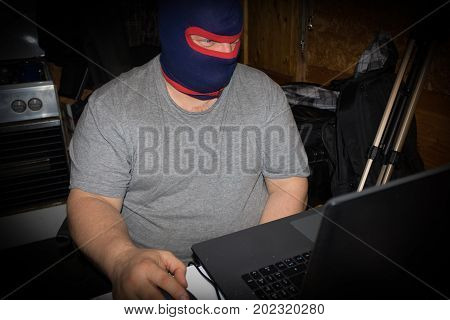Masked Terrorist Working On His Computer. Concept About International Crisis, War, Terrorism ,terror