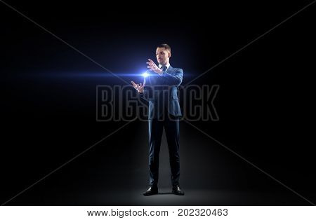 business, people and future technology concept - businessman in suit with laser light over black background