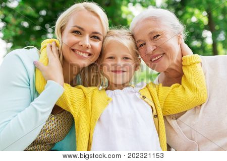 family, generation and people concept - happy smiling woman with daughter and senior mother sitting on park bench