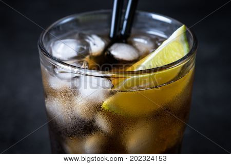 Cuba libre on dark background. Traditional summer alcohol iced drink.
