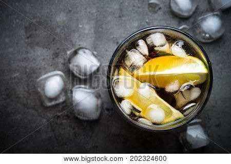 Cuba libre on dark background. Top view. Traditional summer alcohol iced drink.