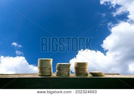 Stack Of Coin In Different Position With Blue Sky With Cloud Background. Money Finance Concept. Mone