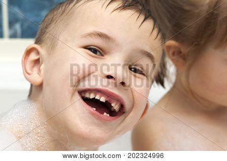 Happily laughing child boy taking a bath. Milk teeth missing