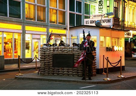 BERLIN - MARCH 27, 2014: Unidentified young man dressed as American soldier stand in front the Checkpoint Charlie in Berlin, Germany. Crossing point between East and West Berlin during the Cold War.