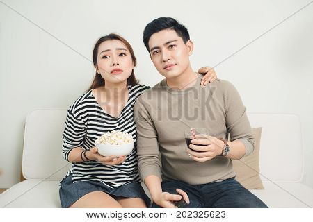 Bored Young Couple Watching Television At Home