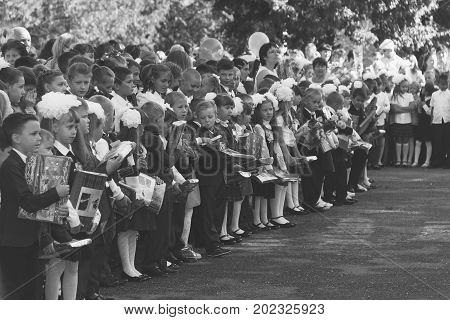 Adygea Russia - September 1 2017: children with bouquets of flowers enrolled in the first class with teachers on the school's solemn line in the day of knowledge black and white photo