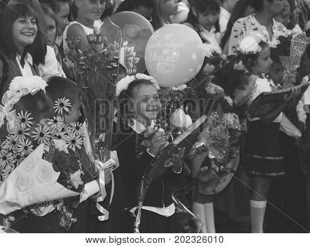 Adygea Russia - September 1 2017: happy children enrolled in the first grade with gifts in hand with teachers and pupils at the school the solemn ruler in day of knowledge a black and white photo