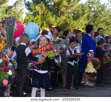 Adygea Russia - September 1 2017: happy children enrolled in the first grade with gifts in hand with teachers and pupils at the school the solemn ruler in day of knowledge