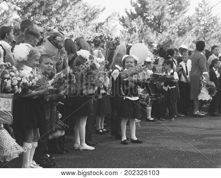 Adygea Russia - September 1 2017: happy children enrolled in the first class with gifts in their hands on the school's solemn line in the day of knowledge black and white photo