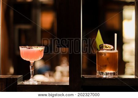 Pink and yellow cocktails garnished with fig and flowers. Alcoholic drinks in bar in margarita and old fashioned glasses
