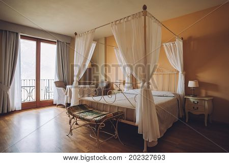 Bedroom In Light Colors. Big Comfortable Double Bed In Elegant Classic Interior